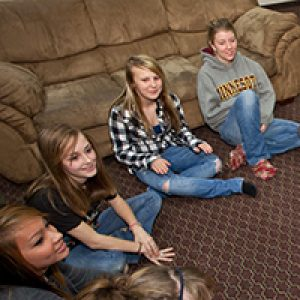 four teenage girls sitting on floor in front of couch