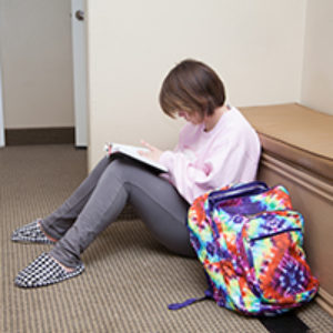 teenage girl reading next to backpack
