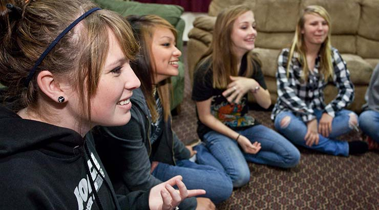 four teenage girls sitting on floor of living room laughing and talking