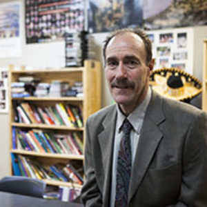 man with mustache in suit in front of bookcases