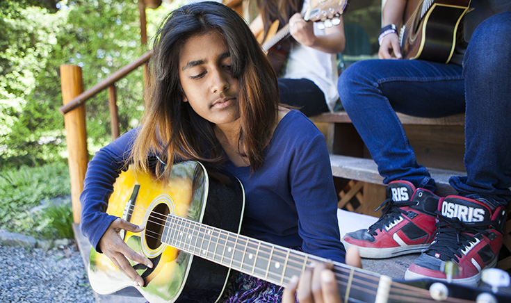 teenage girl playing acoustic guitar