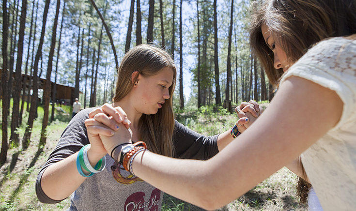 two teenage girls clasping hands in an activity