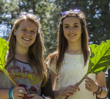 two teenage girls holding leaves
