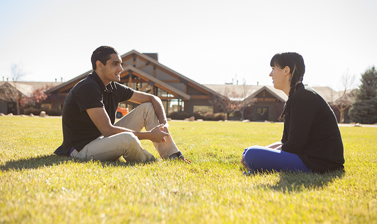 teenage boy and young woman facing each other and talking in grass