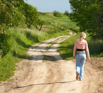 teenage girl in low-cut jeans walking down dirt road