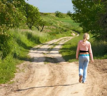 teenage girl in low-cut jeans walking down dirt road