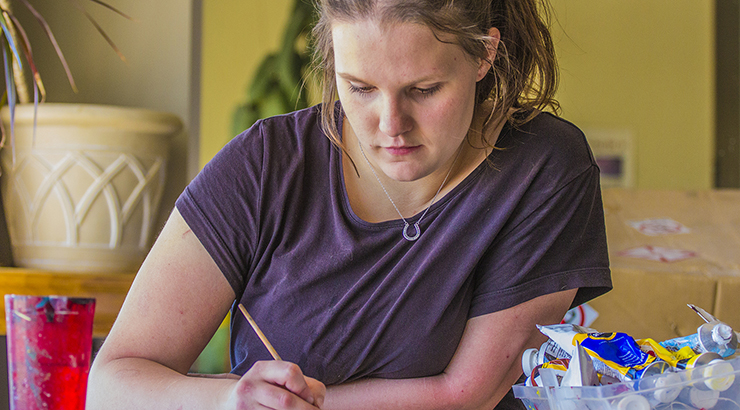 girl in purple shirt writing with a pencil