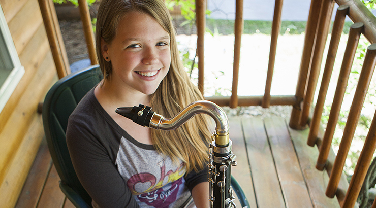 girl sitting on porch with saxophone