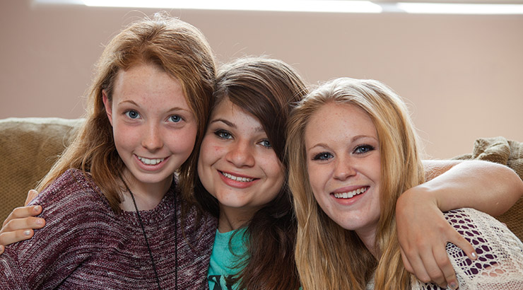 three teen girls sitting on couch with arms around each other