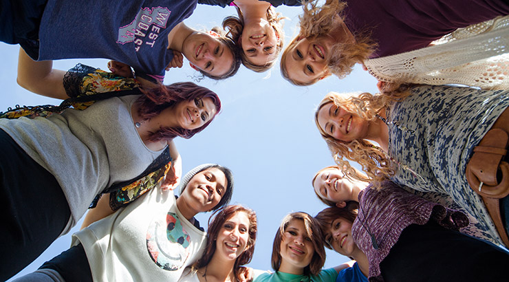 group of teenage girls of different races standing in circle and looking directly at the viewer