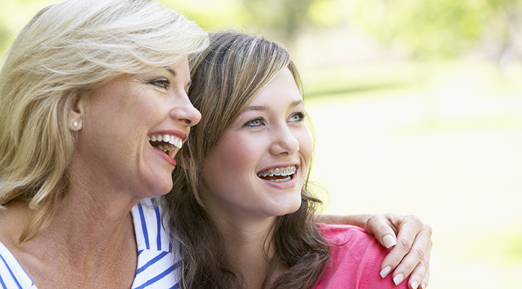 mother with hand around teenage daughter who has braces