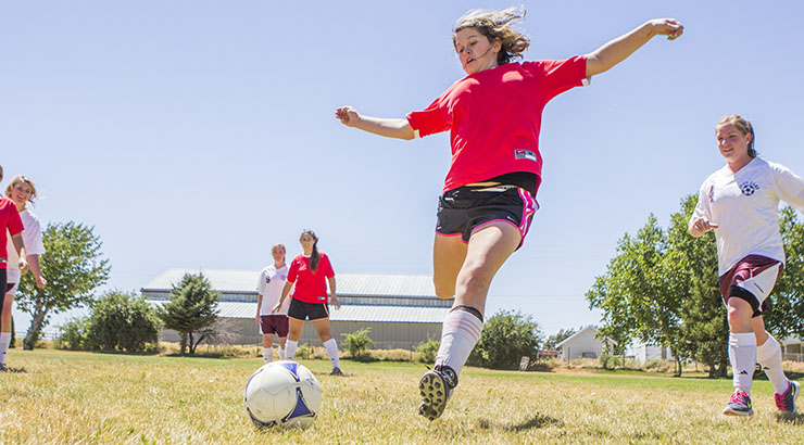 several teenage girls playing soccer
