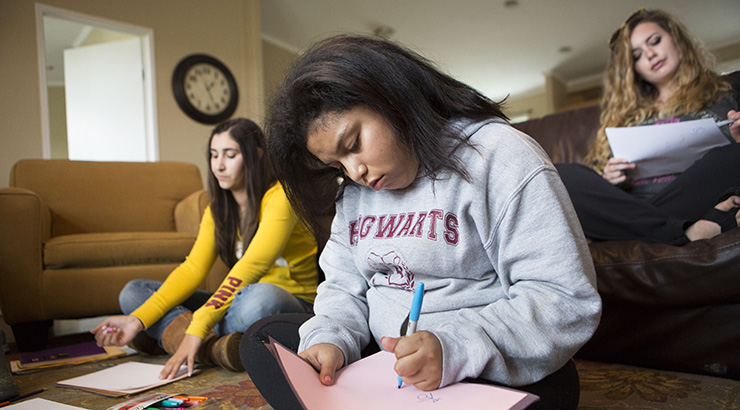 three teenage girls of different races sitting in a living room doing homework