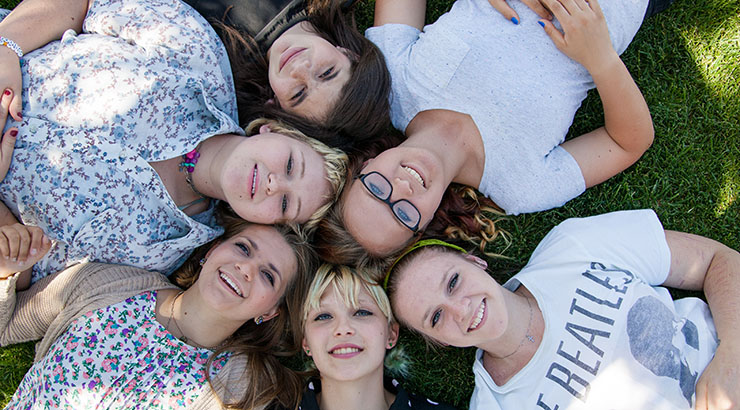 six teenage girls lying on the ground and looking up straight at the camera