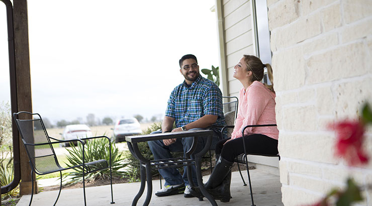man and woman sitting on a porch at a table and talking